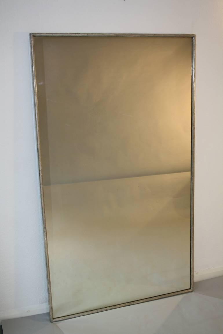 A large narrow framed silver bistro mirror
