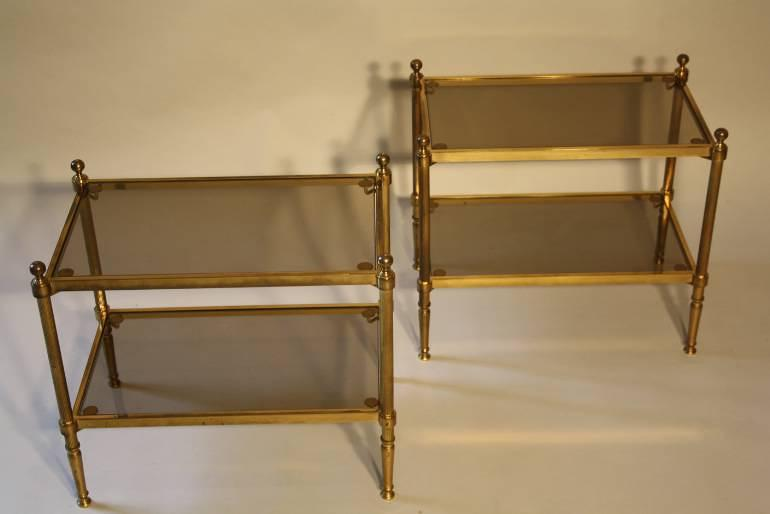 A pair of glass and brass two tier end tables