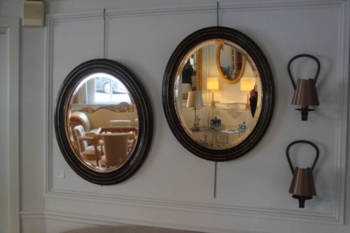 Pair of black ebonised and gold ovals with bevelled glass mirror plate, French Napoleon III c1890