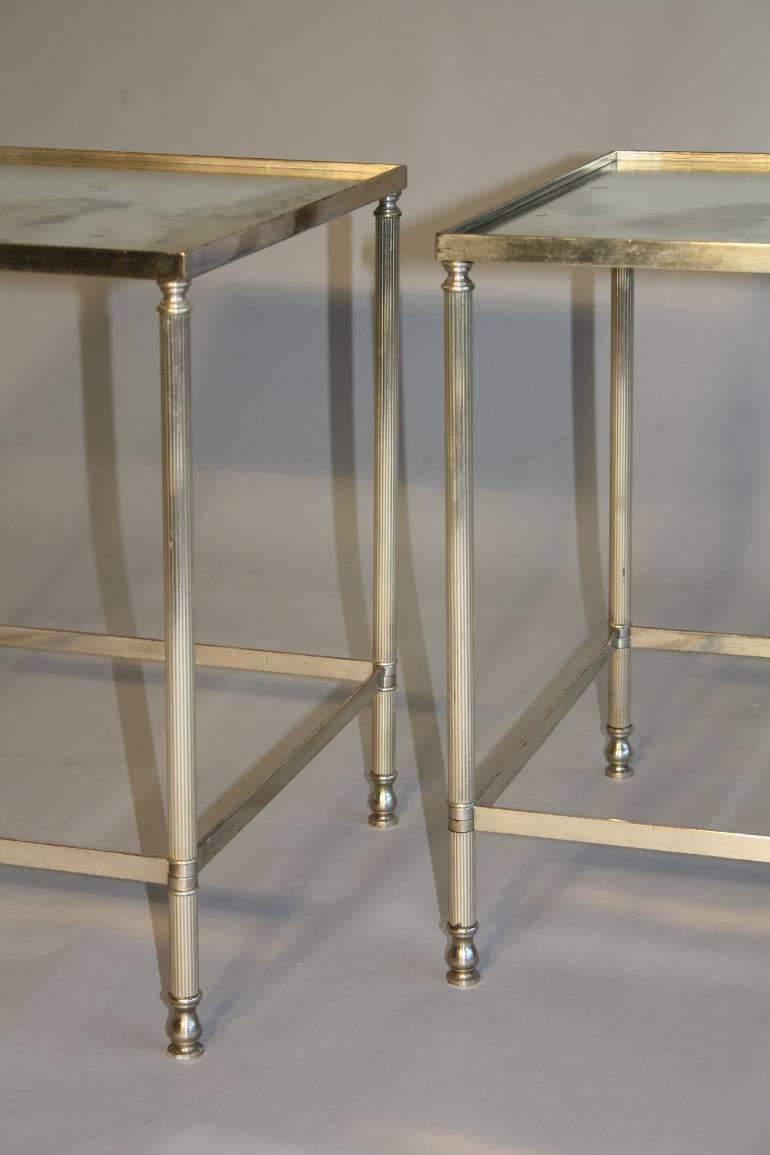 A pair of silver metal bout de canapes (end tables) with slight distressed mirror glass. French c1970