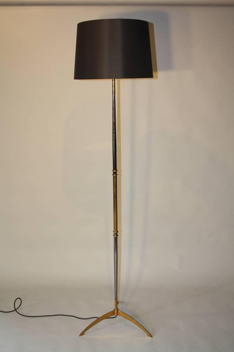 Gun and gold metal tripod floor lamp