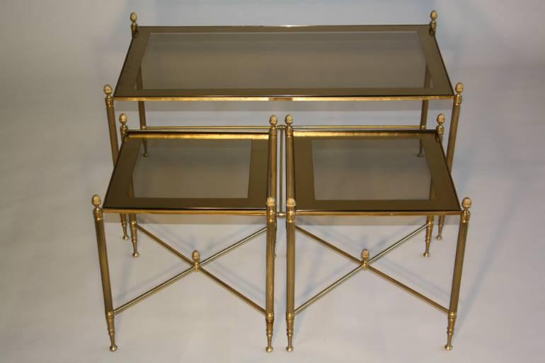 A gilt brass coffee table with two smaller end tables with mirror edged glass. French c1950