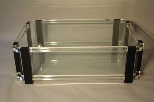 A large black and clear lucite two tier coffee table