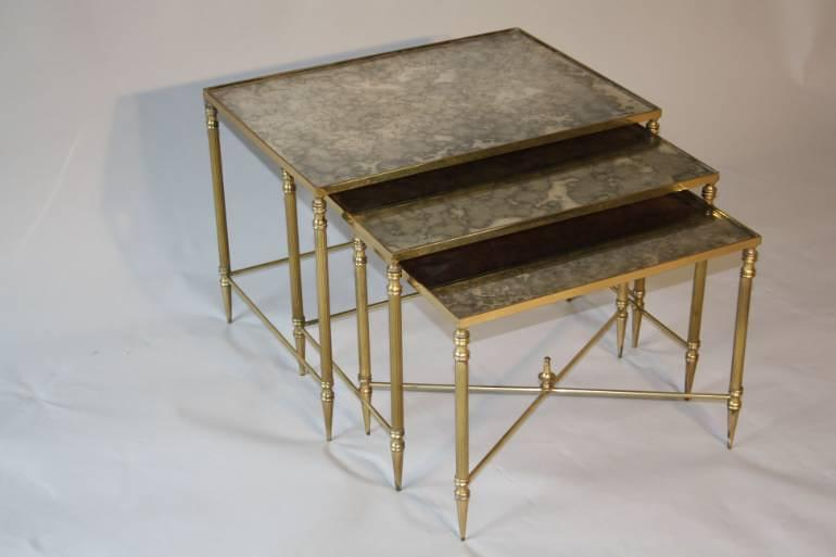 A brass framed nest of tables with antiqued glass.
