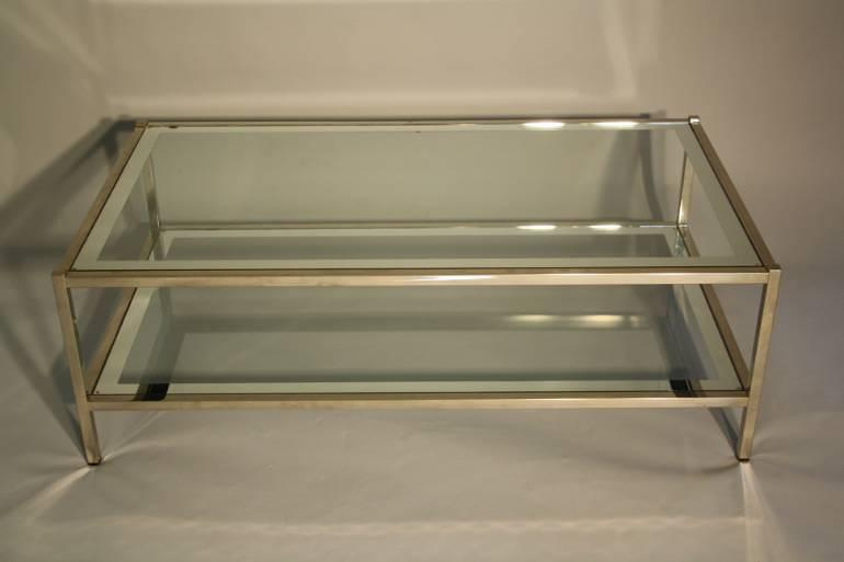 A silver and mirror edged glass two tier table