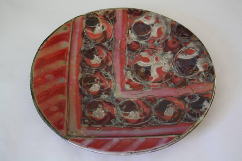 A large red and silver work ceramic plate