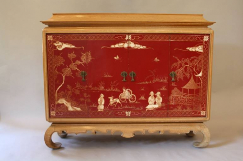 A pagoda Oak cabinet with carved doors depicting Chinese scenes, French c1940