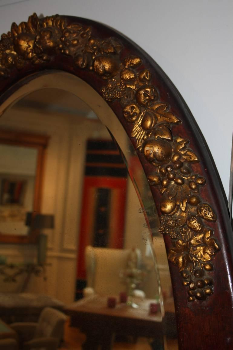 Unusual burgundy painted and gilt Art Deco oval mirror. French c1900