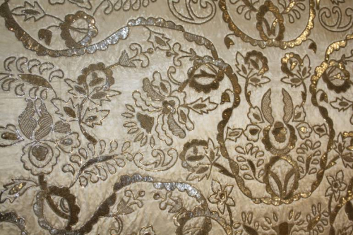 Indian hand stitched sequin textile of stylised flora and fauna on cream silk background. Early 20th