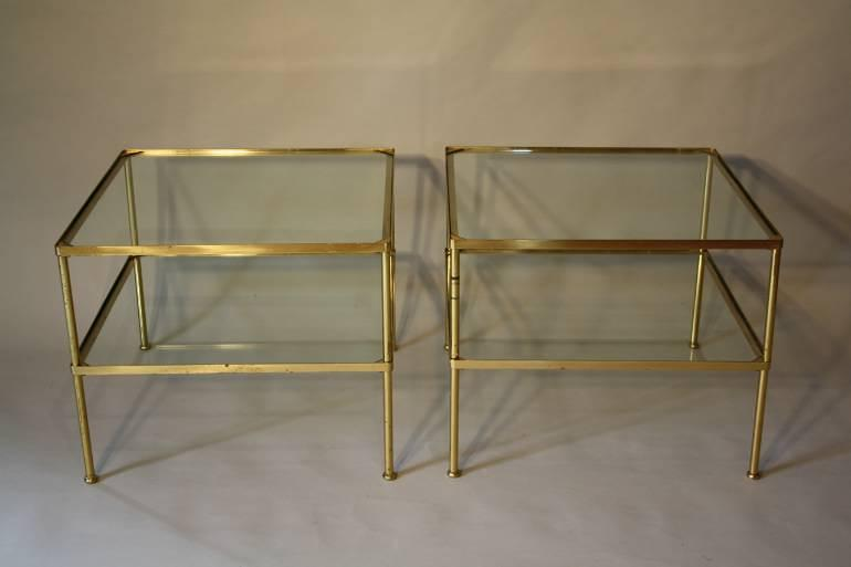 A pair of brass and glass two tier side tables