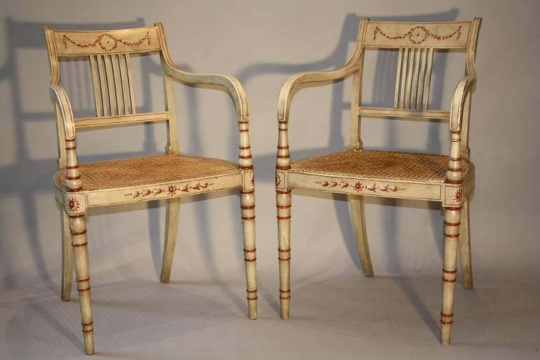 Regency style red and ivory painted open armchairs with cane seats, c1920