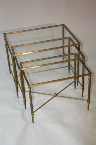 A clear glass and brass nest of tables