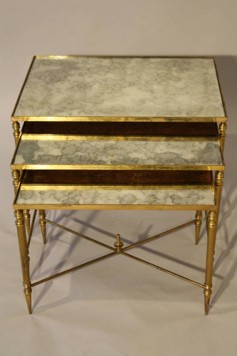 Nest of gilt metal and aged mirror plate side tables