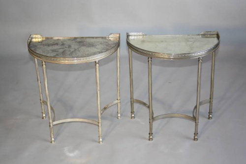 A pair of demi lune silver metal side tables with aged mirror glass tops, French