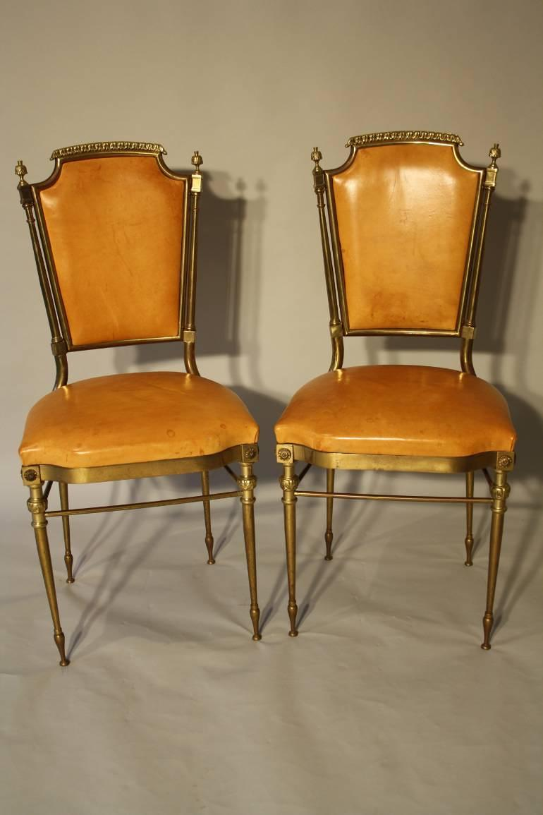 A pair of gilt brass and leather chairs