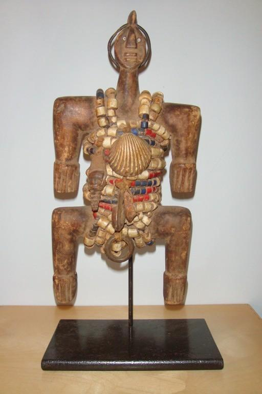 An early C20th  wooden figure decorated with beads and shells from Cam