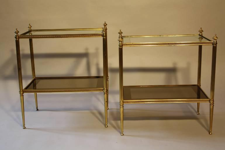 A pair of brass and mirror edge two tier end tables