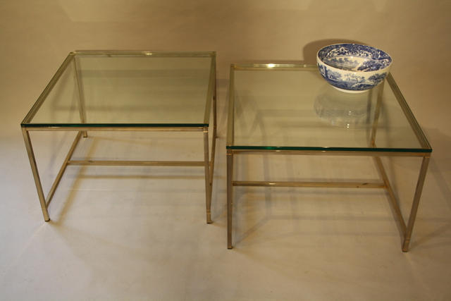 A pair of silver and thick glass tables