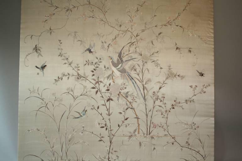 A large hand embroidered textile of birds and flowers