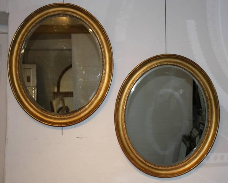 A pair of antique gold leaf oval mirrors, with bevelled glass plates, French c1850