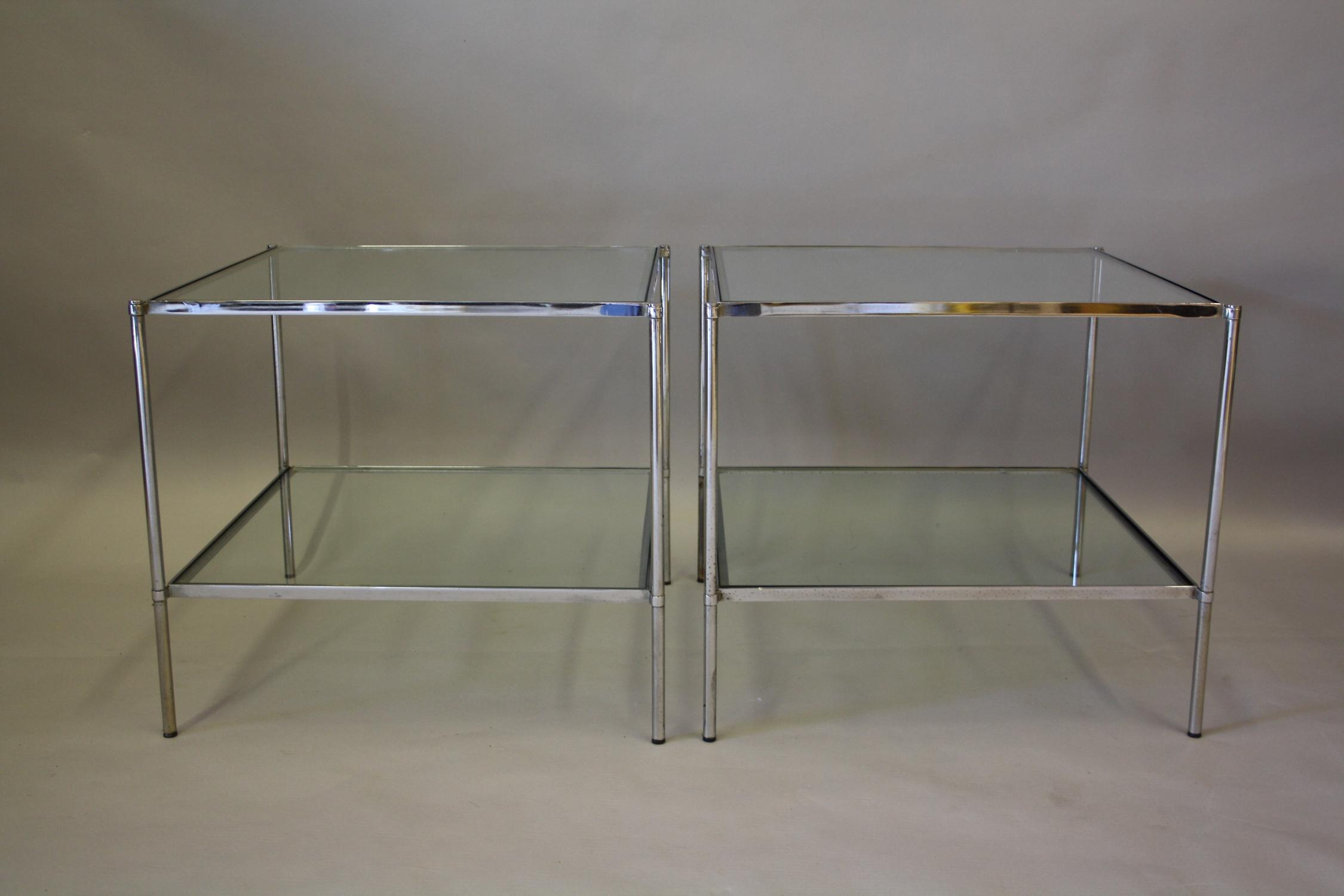 A pair of silver and glass end tables