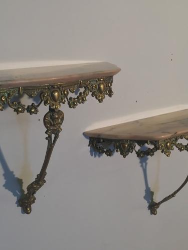 A pair of brass metal and pink marble consoles