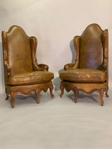Pair of leather wing back armchairs
