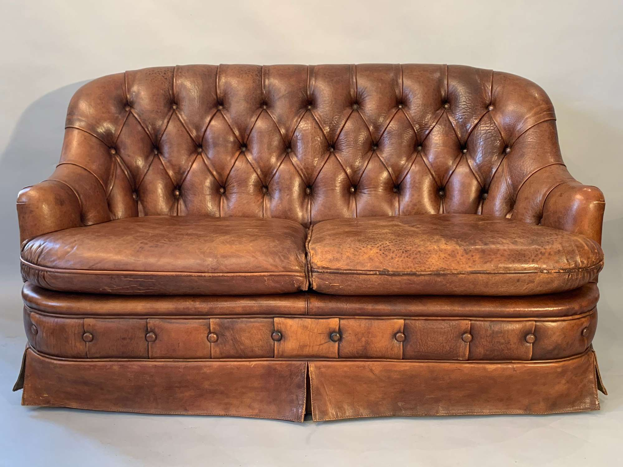 A buttoned tan leather two seat sofa